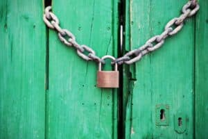 padlock with chain on a green wooden door